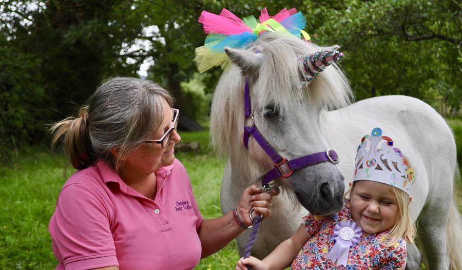 Child posing with a unicorn