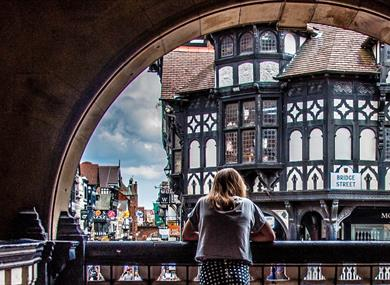Woman looking out over black and white buildings on Bridge Street Chester from the Rows