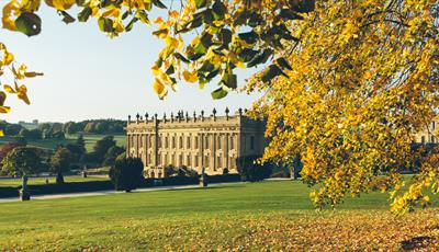 Chatsworth South Front framed by autumn leaves.