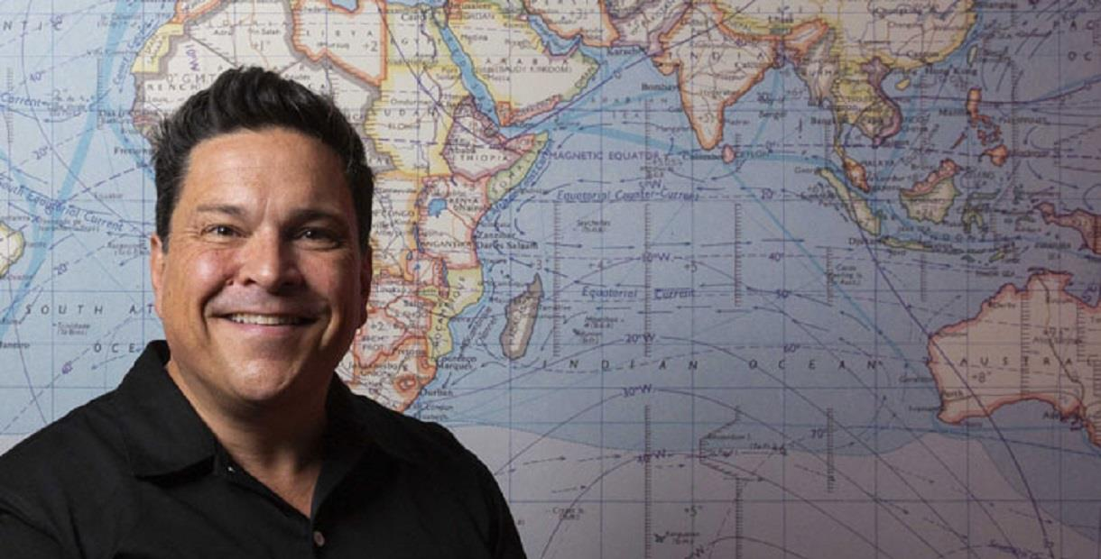 Dom Joly in front of a map of the world