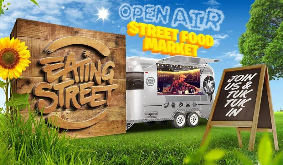 an image of a food truck in a park, a wooden sign reads 'Eating Street', text in the sky reads 'Open Air Street Food Market'