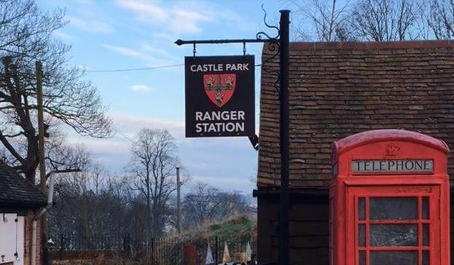 The Castle Park Ranger Station, with its sign containing the colchester coat of arms, with a red telephone box outside