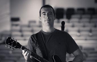 Chris Allard holding a guitar