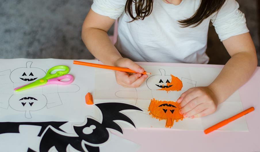 A child colours in pumpkins