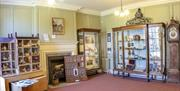 Garden Room at Hollytrees Museum showing Dolls House and cabinet displays