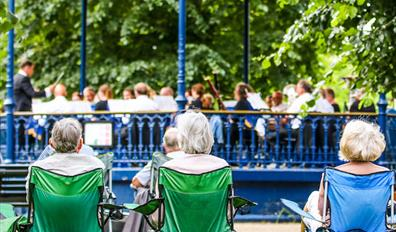 Audience on camping chairs watching a bandstand concert