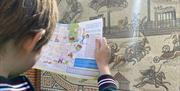 A child reading the map in front of a modern mosaic