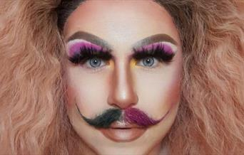 A drag artist with wild blonde hair wearing false eyelashes, pink eyeshadow and a mustache