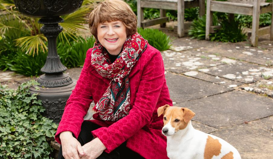 Pam Ayres sitting with her dog in a garden