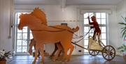 A contemporary sculpture of a chariot racer