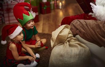 Two children dressed as elves listen to a story read by Santa