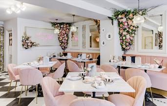 Inside T at The George with pink chairs and pink flower garlands