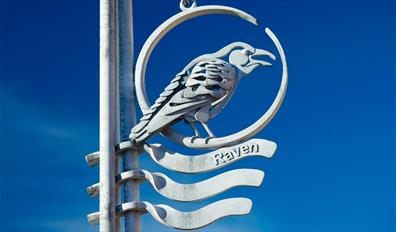 A metallic Raven way marker on the Town to Sea Trail
