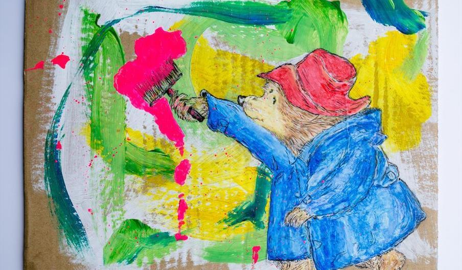An artwork depicting Paddington Bear painting brightly coloured brush strokes on cardboard.