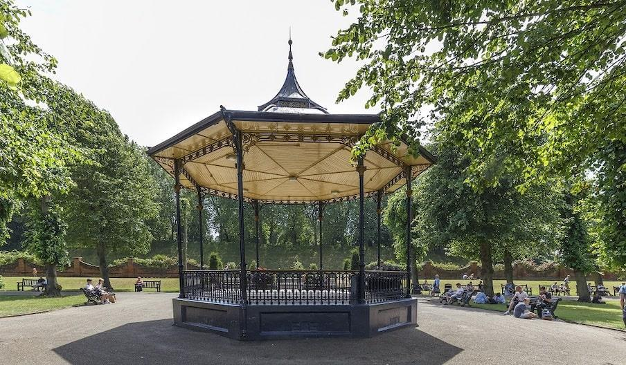 the victorian bandstand in castle park, surrounded by trees and people sitting on wooden benches. the bandstand has dark blue decorative ironwork and