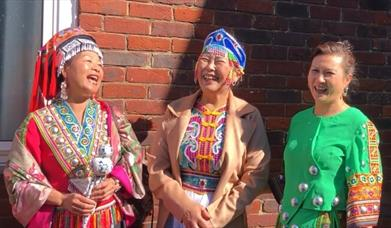 three women standing with their backs against a brick wall, the sun is shining and they are laughing, they are dressed in brightly coloured traditiona