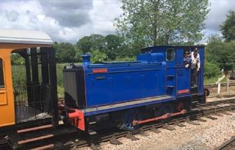 A blue diesel train engine pushing an orange carriage