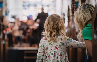A toddler watches an Orchestra play