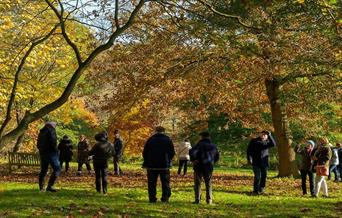 A crowd of people in autumnal parkland