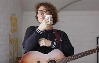 Kevin Pearce with a cup of tea and acoustic guitar