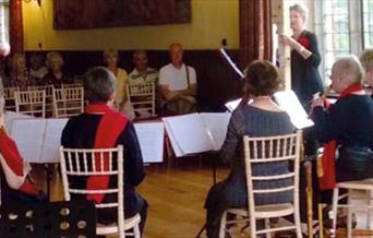 six musicians play to a small audience in a wood panelled hall with a large window