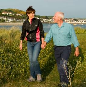 Couple walking and holding hands along Wales Coast Path
