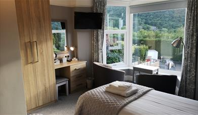 Twin room with with cream linen and tv on the wall. Large window overlooking the scenery.