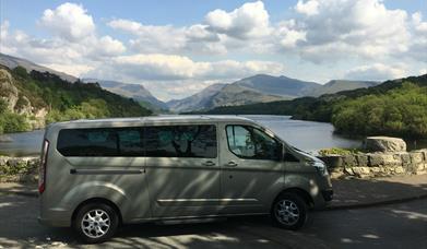 mini tour bus parked next to lake with views of the Snowdonia Range