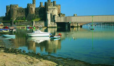 Conwy Castle with Conwy railway bridge to the right of the image and Conwy estuary in the foreground