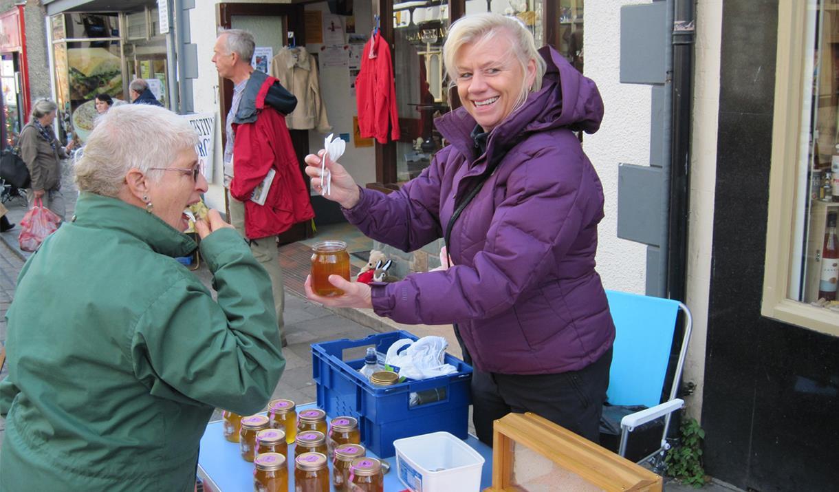 Image of customer sampling honey at a stall at the Conwy Honey Fair
