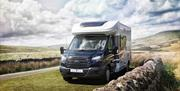 Image of motor home parked on a grass patch in the countryside