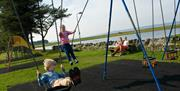 Children playing on the swings in the play area, Llanfairfechan Seafront