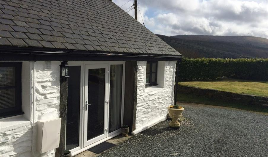 External image of white exposed brick cottage with views of the mountains