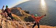 Young child abseiling over cliff edge with ocean in the background