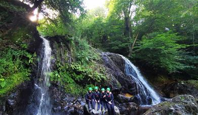 Young people sitting on rock edge next to waterfalls