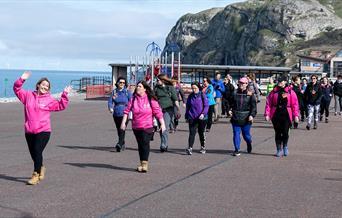 Image shows people walking on Llandudno Promenade