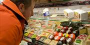 Man perusing the cheese selection at Blas ar Fwyd, Llanrwst
