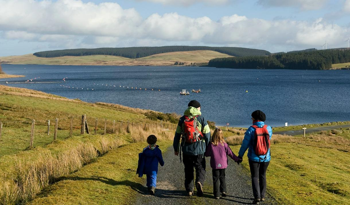 Family walking towards Llyn Brenig