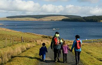 Family walking towards Llyn Brenig