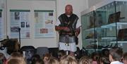 Man dressed as Roman soldier talking to children inside Llandudno Museum