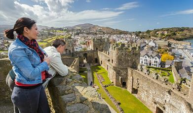 People looking into the interior of Conwy Castle from the turrets