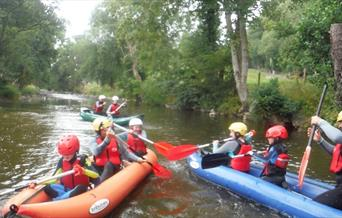 Groups of children and adults enjoying rafting on the river