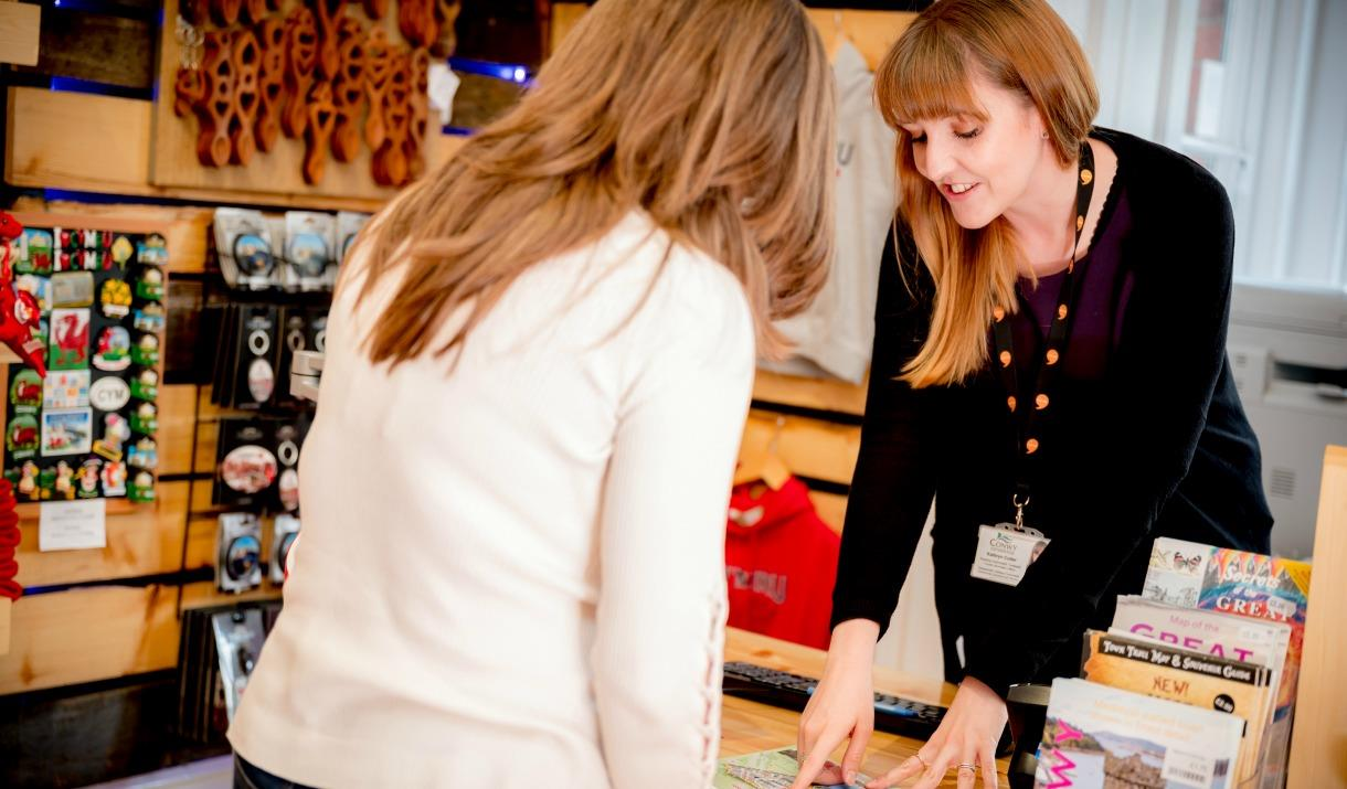 A member of staff in the Tourist Information Centre showing a customer the attractions in Conwy.