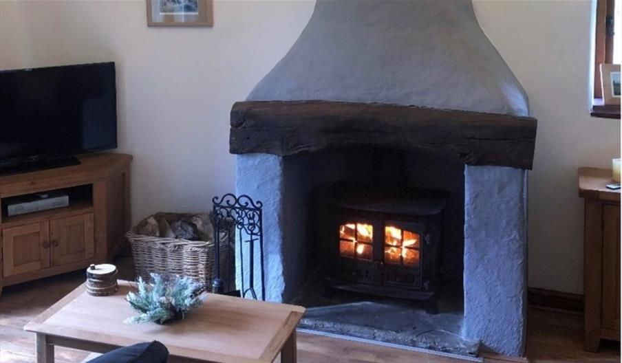 Lit  fire place with a stone surround chimney with a TV unit in corner of the room