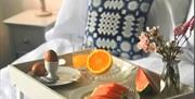 Image of a bed with a breakfast table displaying fresh watermelon, boiled egg and flowers