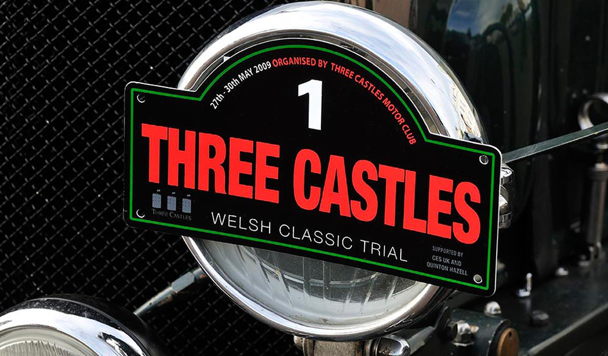 Image shows Three Castles sign on front of classic car