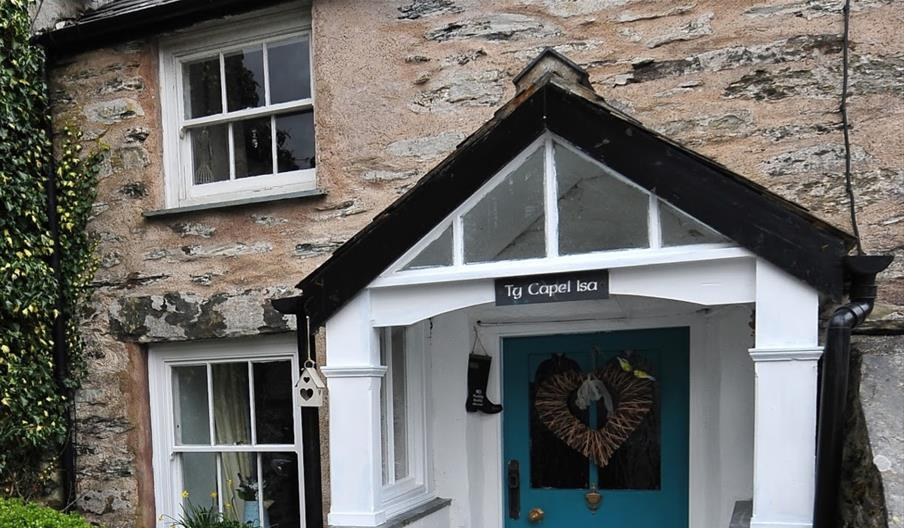 Image of stone cottage with sash windows with a teal front door and heart shaped wreath on the front.