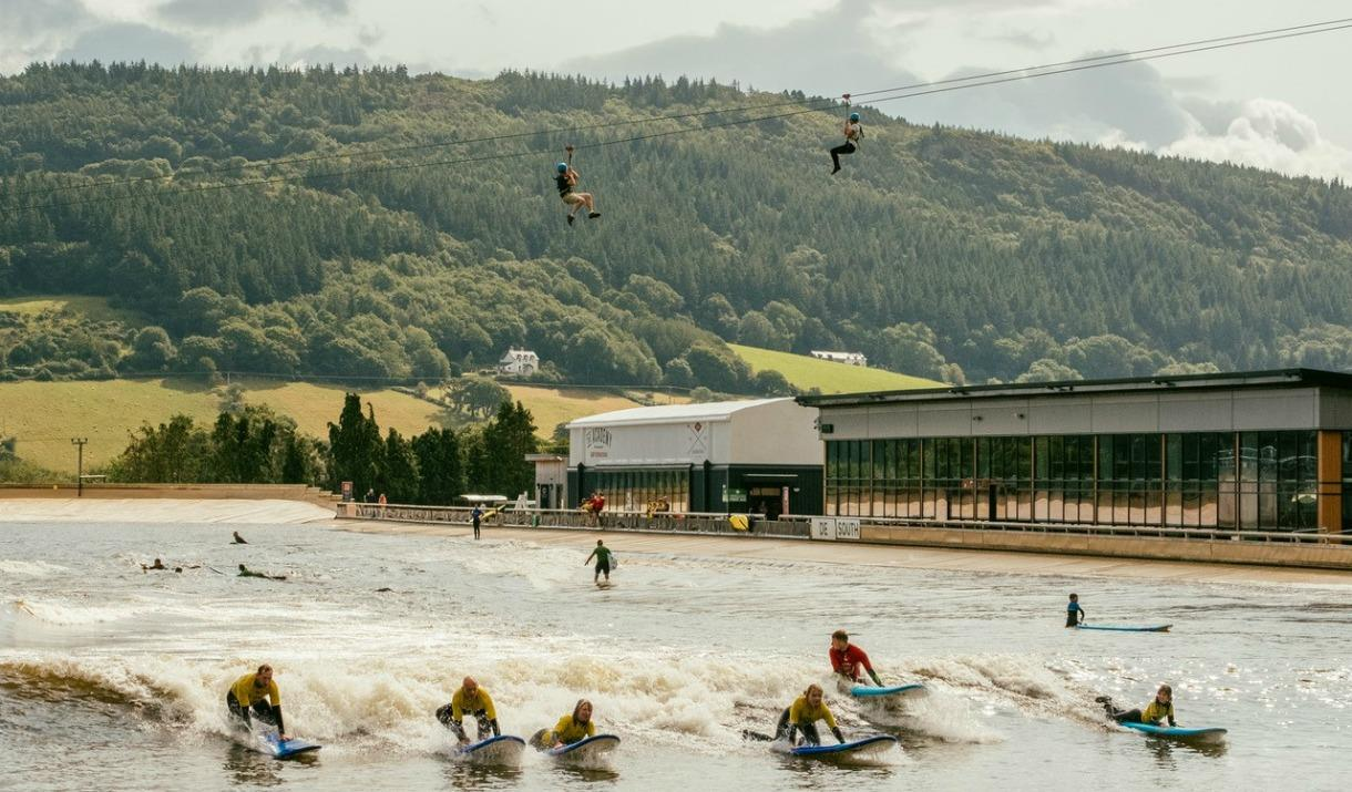 Surfers on the waves and zip wire users flying above water