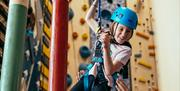 Child descending on rope from climbing walls