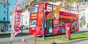 Red City Sightseeing bus parked by its advertising banners
